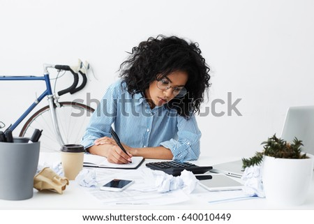 Attractive young dark-skinned female columnist suffering from writer's block, working on new article for online women's magazine, making notes in sketchbook, surrounded by crumpled paper balls