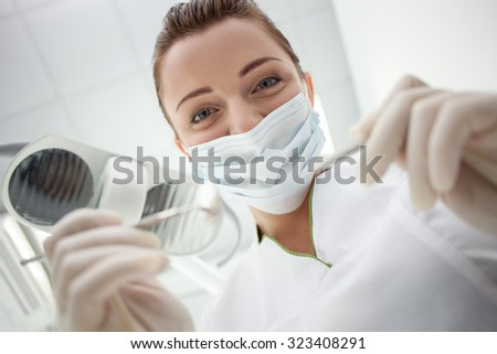 Attractive young dentist is treating her patient. She is standing and holding tools under her patient. The woman is looking down with happiness. Focus on her hands - stock photo