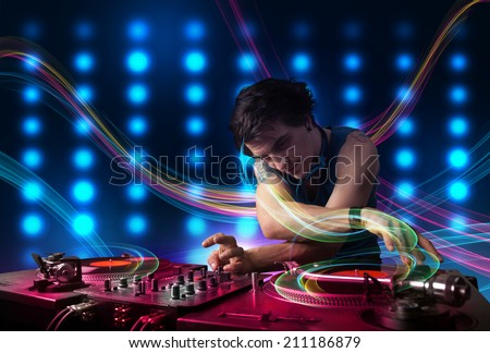 Attractive young Dj mixing records with colorful lights - stock photo