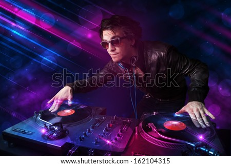 Attractive young DJ playing on turntables with color light effects - stock photo