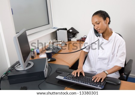 Attractive young doctor on the phone in her office - stock photo