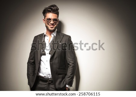 Attractive young elegant business man smiling while holding both hands in his pocket. - stock photo