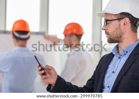 Attractive young engineer is calling to his client. He hopes that the customer will approve the plan of building. He is looking at mobile phone with concentration. His crew is working on background