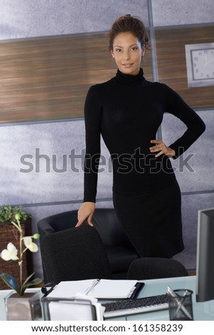 Attractive young ethnic businesswoman standing in black at desk in modern office.