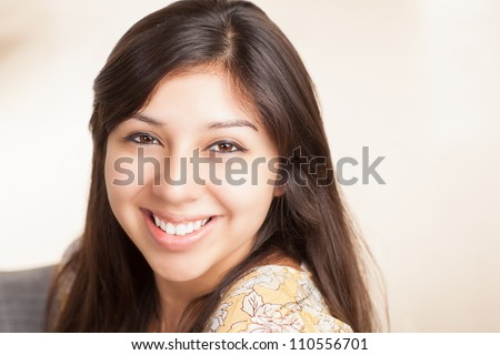 Attractive young ethnic woman in living room wearing festive yellow shirt with flowers. - stock photo