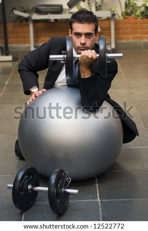 Attractive young executive doing biceps curls in a gym, dressed in a business suit. His face is framed by the weights he's curling. - stock photo