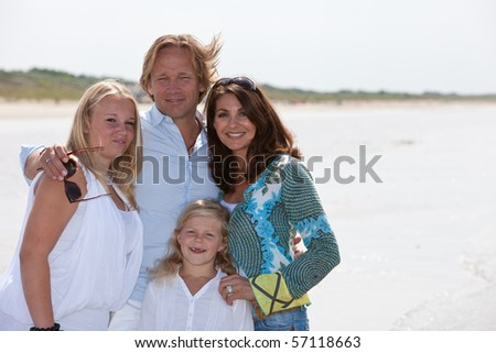 Attractive young family of four by the waterside in the summer