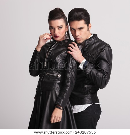Attractive young fashion man holding his girlfriends shoulders while looking at the camera. - stock photo
