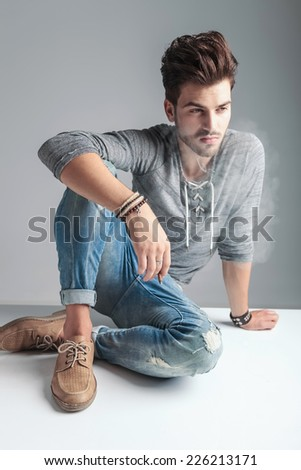 Attractive young fashion man looking down while holding a cigarette in his right hand, relaxing on the floor.