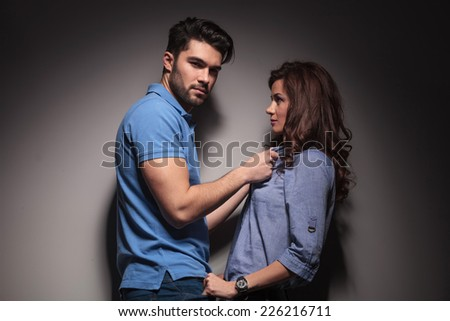 Attractive young fashion man pulling his girlfriends collar while looking at the camera. - stock photo