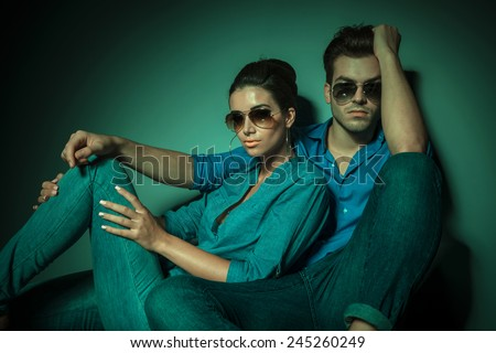 Attractive young fashion man sitting an leaning on a wall while his girlfriend is leaning on him, both looking at the camera. - stock photo
