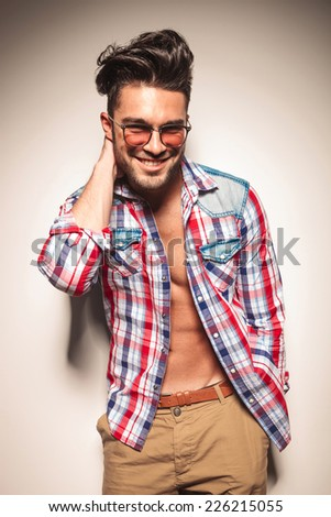 Attractive young fashion man smiling for the camera while holding one hand to his neck and the other in his pocket. - stock photo