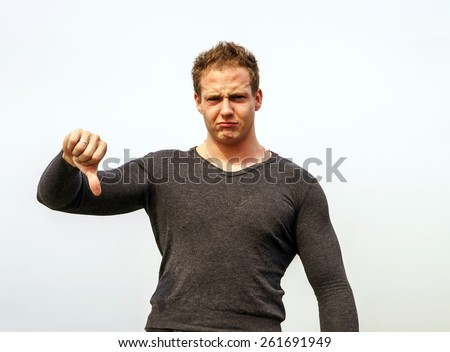 Attractive young fashion man smiling to the camera while showing the thumbs down gesture - stock photo