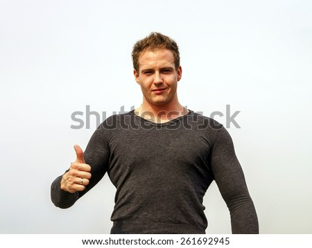 Attractive young fashion man smiling to the camera while showing the thumbs up gesture - stock photo