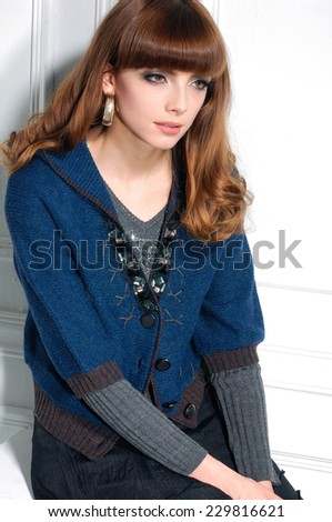 Attractive young fashion model in near door sitting cube - stock photo