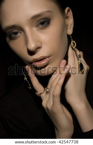 Attractive young fashionable model posing on deep black background - stock photo