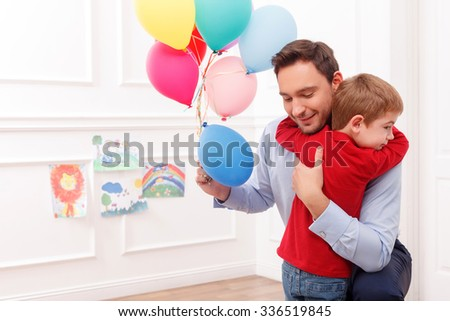 Attractive young father is giving the present to his son. He is holding balloons and smiling. The man is kneeling. The boy is embracing him with love - stock photo