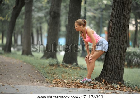 Attractive young female athlete in park - stock photo