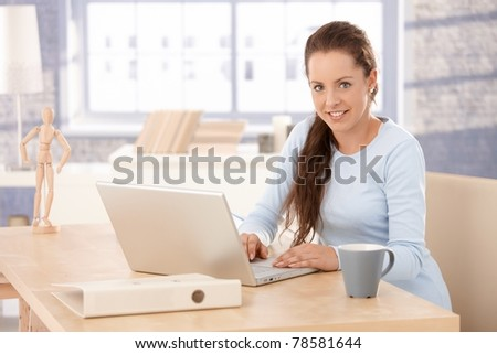 Attractive young female browsing internet at home, sitting at desk, using laptop, smiling.?