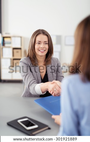 Attractive Young Female Business Agent Shaking Hands with the Client While Sitting at the Table Inside the Office. - stock photo