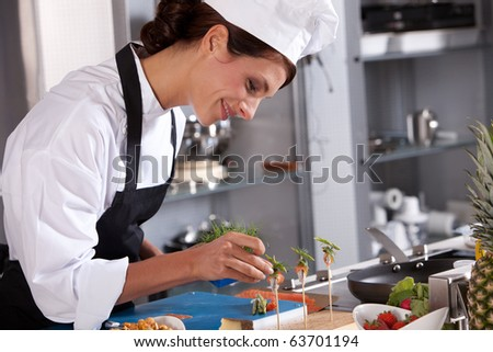 Attractive young female chef adding some garnish to the amuse - stock photo