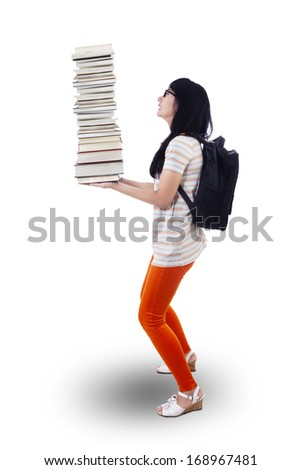 Attractive young female college student carrying a stack of books - stock photo