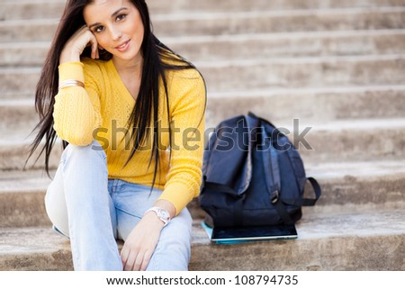 attractive young female college student sitting outdoors - stock photo