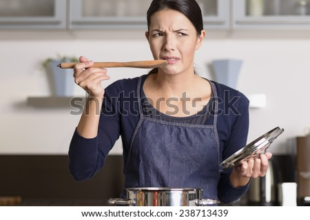 Attractive young female cook standing at the hob in her apron tasting her food in the saucepan with a grimace as she finds it distasteful and unpalatable - stock photo