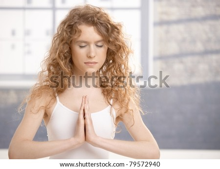 Attractive young female doing yoga exercise, meditating in prayer pose, eyes closed, sitting on floor front of window.? - stock photo