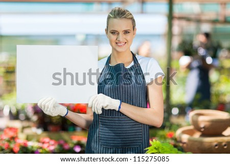 attractive young female florist holding white board in greenhouse - stock photo