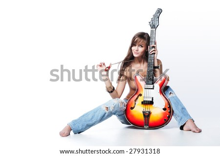 Attractive young female holding a guitar - stock photo