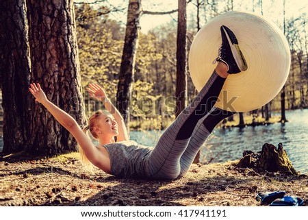 Attractive young female in sportswear exercising with fitness ball in a sunny forest. - stock photo