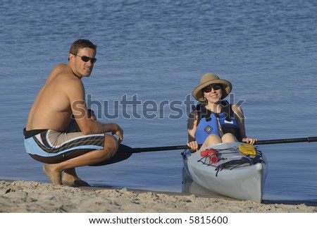 Attractive young female kayaker and her instructor on the beach at Mission Bay, San Diego, California. - stock photo