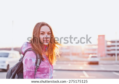 Attractive young female looking to camera on a parking lot at a sunset. Traveling, life and freedom concept. Copy space - stock photo