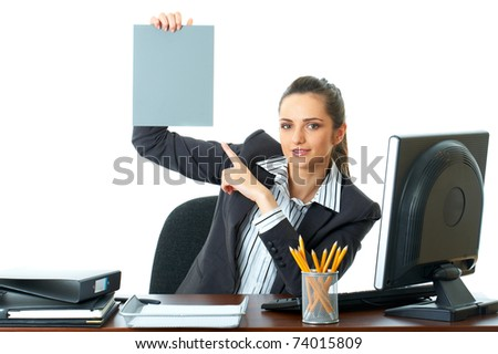 attractive young female office worker holds empty grey card in front of her, point to it with her finger, isolated on white