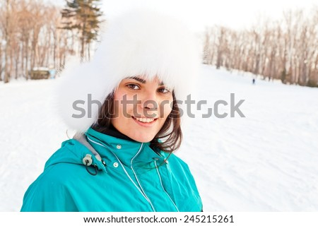 Attractive young female on a ski resort. Friendly smiling young woman wears fur hat and ski clothes. Standing back to slope and forest. Head-shot portrait - stock photo