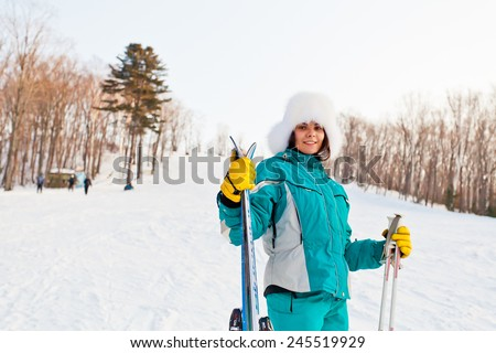 Attractive young female on a ski resort. Friendly smiling young woman wears fur hat and ski clothes. Hands poles and skis. Standing back to slope and forest. Half-length portrait - stock photo