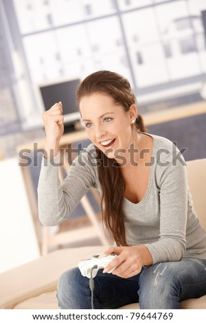 Attractive young female playing video game at home, having fun, laughing.? - stock photo
