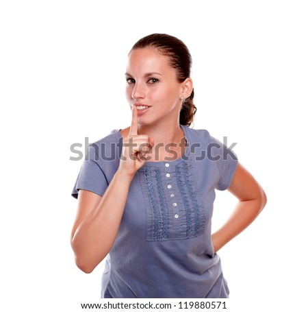 Attractive young female requesting to you silence on blue shirt against white background - stock photo