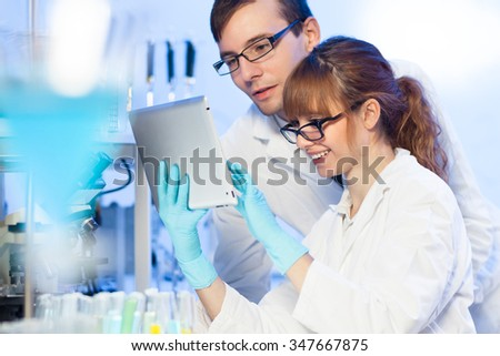 Attractive young female research scientist and her post doctoral male supervisor looking focused at the tablet in the life science laboratory. - stock photo