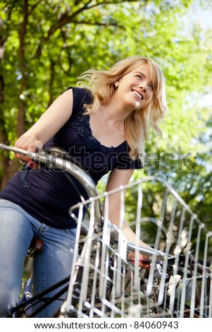 Attractive young female riding a bike through green nature - stock photo