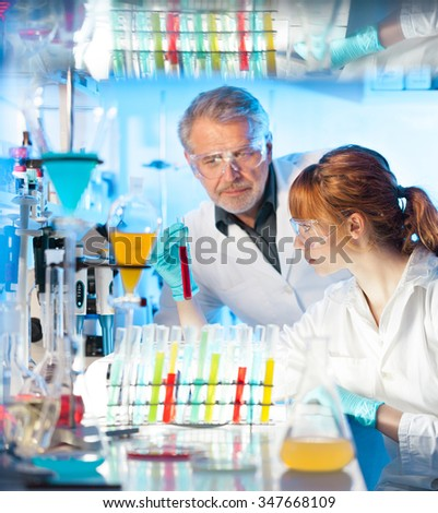 Attractive young female scientist and her senior male supervisor looking at the cell colony grown in the petri dish in the life science research laboratory. - stock photo