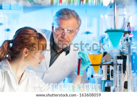 Attractive young female scientist and her senior male supervisor observing color shift of a liquid in the glass tube in the life science research laboratory (biochemistry, genetics, forensics,..) - stock photo