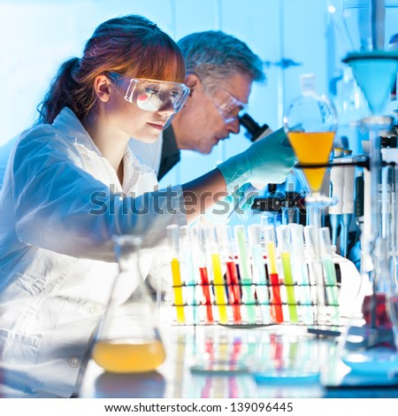 Attractive young female scientist and her senior male supervisor pipetting and microscoping in the life science research laboratory (biochemistry, genetics, forensics, microbiology..) - stock photo