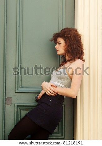 attractive young female sitting and waiting by a door