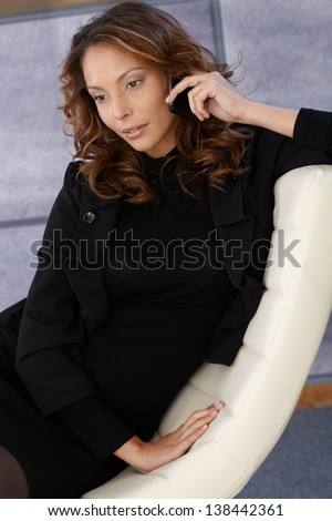 Attractive young female talking on mobile in design chair.