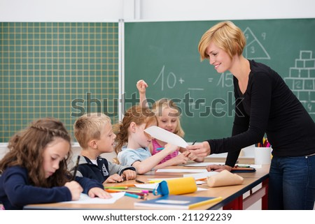 Attractive young female teacher checking a young boys work as he sits working on a project with other students at a long table - stock photo