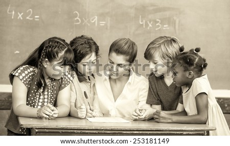 Attractive young female teacher checking multi race classroom work with other students at the desk. - stock photo