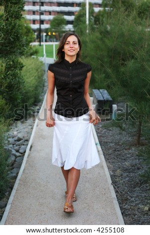 Attractive young female walking at the park - stock photo
