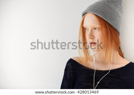 Attractive young female with red hair and healthy freckled skin looking away with dreamy expression, listening to her favorite music with earphones, against white copy space wall for your information  - stock photo